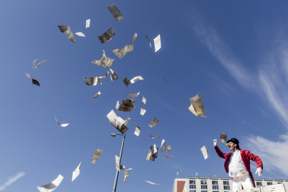BERLIN, GERMANY - SEPTEMBER 29:  An activist dressed as Scrooge McDuck throws counterfeit money from a golden mountain onto protesters during a demonstration against the increasing gap between wealth and poverty on September 29, 2012 in Berlin, Germany. The demonstration is part of a nationwide day of action.  (Photo by Carsten Koall/Getty Images)